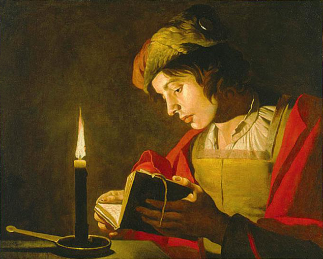 matthias_stom_young_man_reading_by_candlelight.jpg