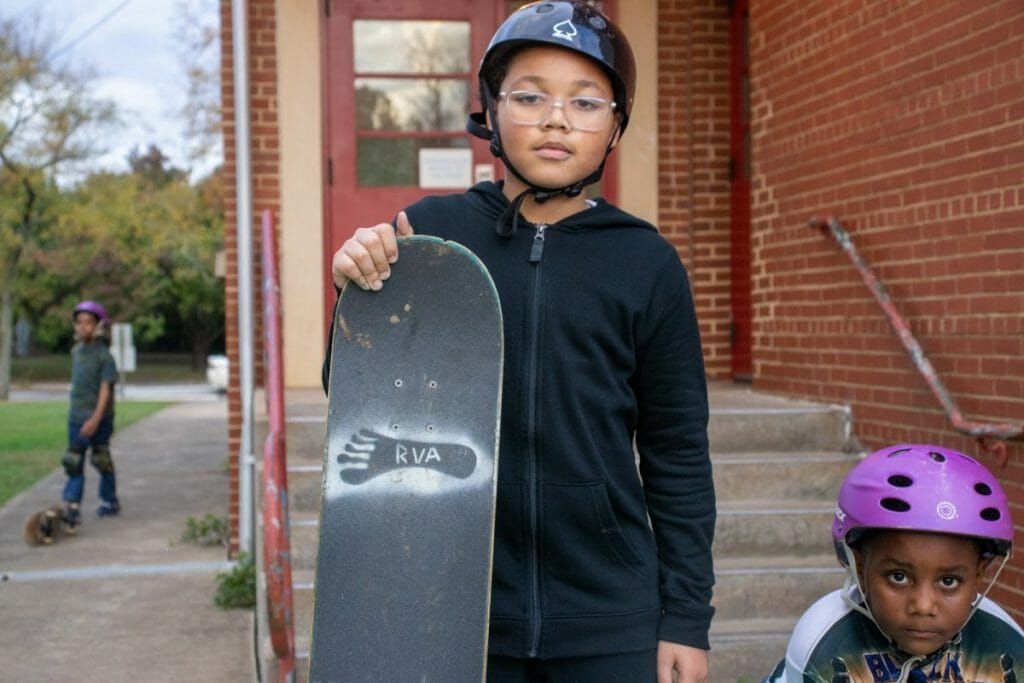 "Young skateboarder holding skateboard featuring ""RVA"" stencil"